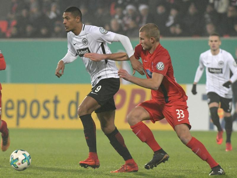Heidenheims Timo Beermann (r) und Sebastien Haller von Eintracht Frankfurt kämpfen um den Ball. Foto: Stefan Puchner