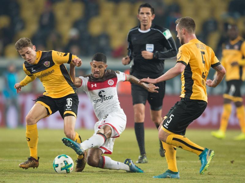 St. Paulis Jeremy Dudziak (M) setzt sich im Kampf um den Ball gegen die Dresdner Niklas Hauptmann (l) und Manuel Konrad (r). Foto: Sebastian Kahnert